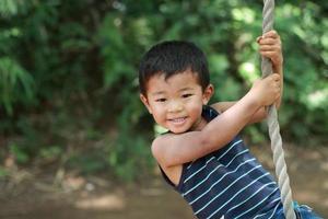 japansk pojke som leker med tarzan rep foto