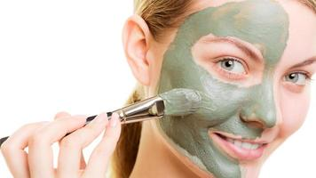 kvinna ansöker med borste lera lera maskera hennes ansikte foto