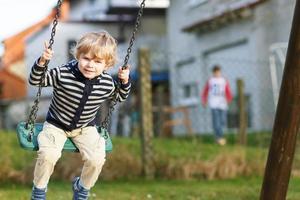 bedårande litet barnpojke som har roligt kedjesving på utomhuslek foto