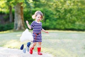 liten flicka springer i park med röda gummistövlar foto