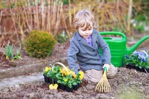 liten pojke som arbetar i trädgården och planterar blommor i trädgården foto