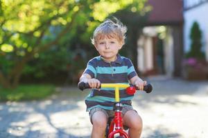 liten pojke på 3 år som har kul på sin cykel