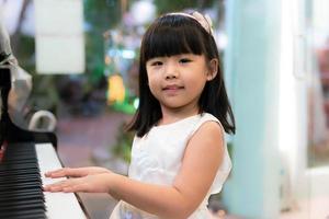 liten flicka i en vit klänning som spelar piano foto