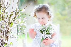 vacker barnflicka som håller första vårblommor i transparent vas foto