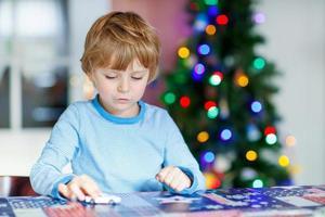 litet blondt barn som leker med bilar och leksaker vid jul foto
