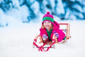 liten flicka som leker i snöig vinterskog foto
