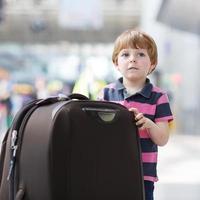 liten pojke som åker på semesterresa med resväska på flygplatsen foto