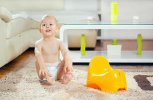 liten pojke som sitter nästa potta foto