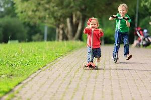 liten pojke och småbarn tjej ridning skotrar i sommaren park