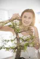 vacker kvinna som tar hand om en bonsai foto
