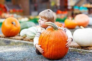 liten gullig pojke som sitter med enorm pumpa på halloween foto