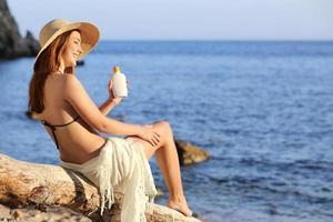 kvinna på semester på stranden tillämpar solskyddsskydd foto