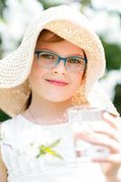sommar liten flicka i stråhatt dricksvatten utomhus porträtt. foto
