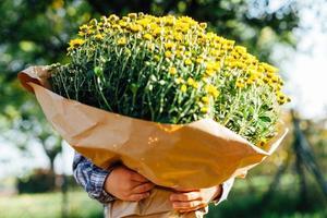 liten pojke som gömmer sig bakom en stor bukett med gula blommor foto