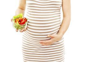 den unga gravida kvinnan med grönsaker foto