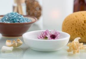 spa-koncept med flytande blommor badsalt och badsvamp foto