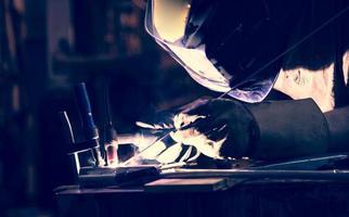 anställd svetsar aluminium med tig svetsare.