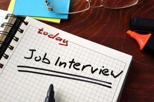 anteckningsbok med tecken på jobbintervju på ett bord. affärsidé. foto