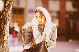 tjej letar efter något i en väska foto
