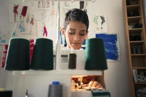 ung kvinna på jobbet som skräddare i modedesign atelier foto