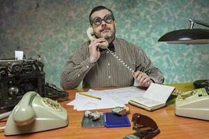 anställd med glasögon som pratar i telefon på kontoret foto
