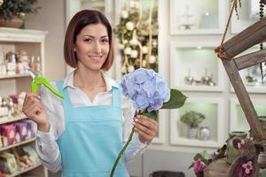 vacker ung försäljare arbetar i blomsterbutik foto
