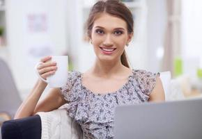 attraktiv affärskvinna som sitter på skrivbordet på kontoret foto