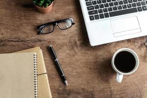 bärbar dator och kopp kaffe på gamla träbord, foto