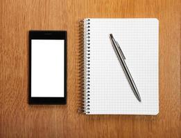 affärs- och utbildningskoncept - smartphone och anteckningsblock foto