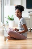 afroamerikansk kvinna som använder en bärbar dator i sitt vardagsrum
