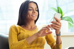 avslappnad kvinna med smartphone foto