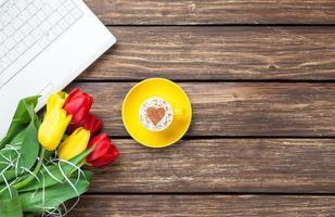 kopp cappuccino med hjärtaform och dator foto