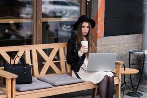 ung kvinna njuter av kaffe under arbetet på bärbar bärbar dator foto