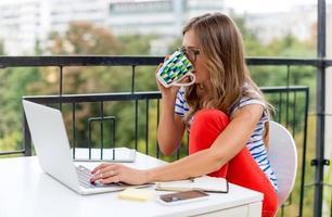ung kvinna med ett kaffe på terrassen foto