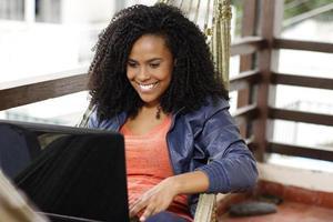 brunett kvinna med dator på hängmattan foto