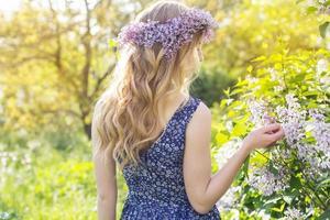 flicka med krans från lila blommor i grön park