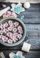 wellnessuppsättning med skål med vatten och blommor, kroppsbehandling foto