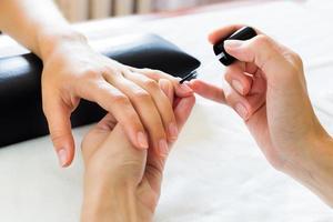 manikyrist som sätter mjukgörare på nagelbanden foto