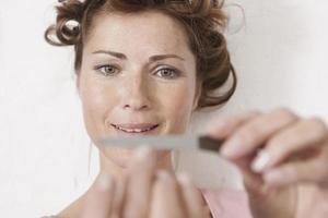 Tyskland, kvinna arkiverar naglar leende foto