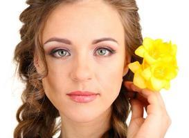 ung kvinna med vacker frisyr och blommor, isolerad på vitt foto