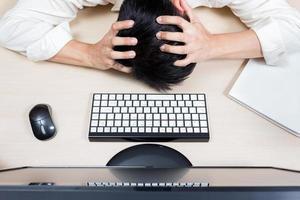 trött & huvudvärk asiatisk affärsman eller anställd arbetar övertid foto
