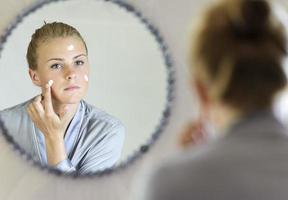 vacker ung kvinna applicerar ansiktskräm foto