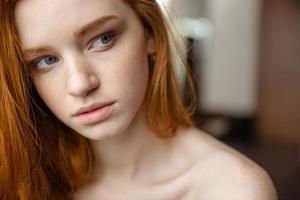 skönhet porträtt av fundersam kvinna med rött hår tittar bort foto