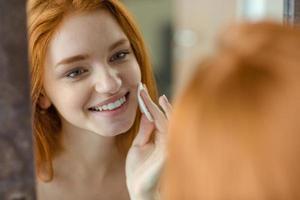 kvinna med vadd tittar på hennes reflektion i spegel foto