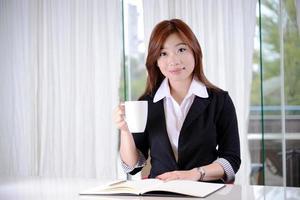 attraktiv affärskvinna som rymmer en mugg foto