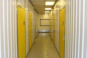 vit industriell korridor med gula numrerade dörrar foto