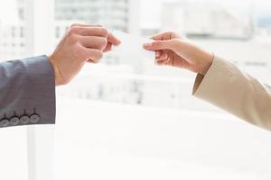 närbild av händer som håller visitkort foto