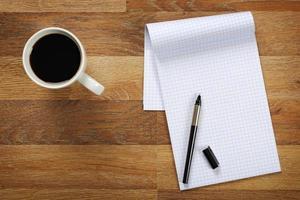 ovanifrån på skrivbordet med anteckningsblock och kopp kaffe. foto