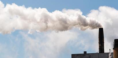 pappersbruk smokestack vit rök blå himmel foto