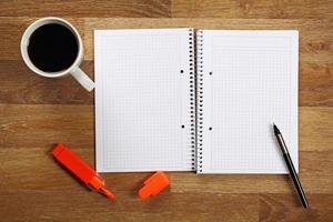 öppnade anteckningsboken och en kopp kaffe på skrivbordet. foto